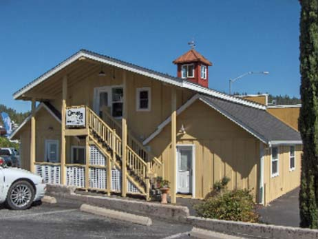 AFTER construction, roofs extend over the rear stairs to the upper level. The original character was retained by keeping the two  rooflines of the original single-story cabins (at the left and right of the lower level).