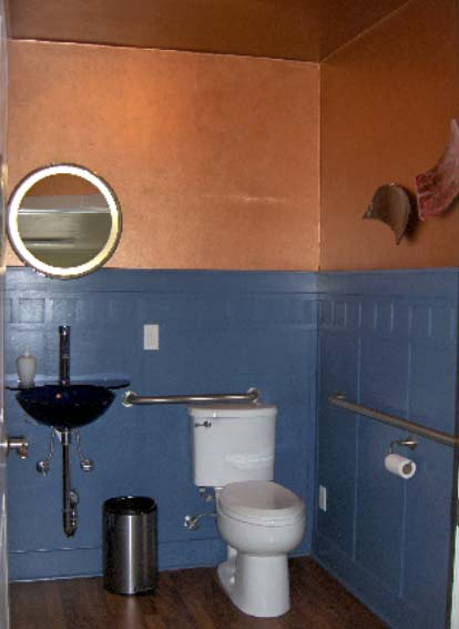 Downstairs, a new wheelchair  accessible bath was added. But rather than feeling drab and institutional, it has vibrant blue wainscot  contrasting with copper above.