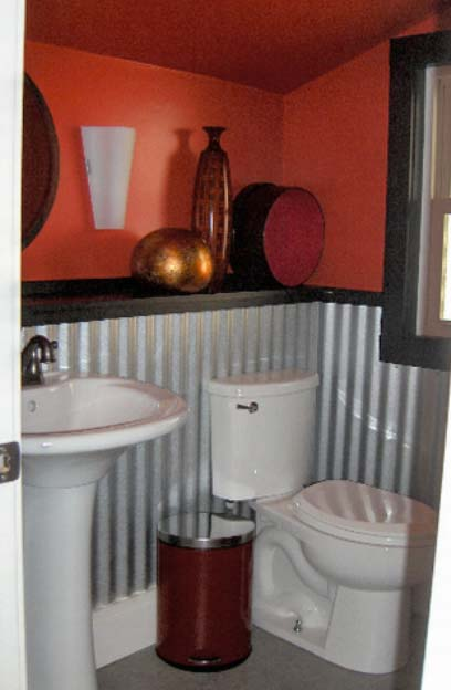 Upstairs, the one-of-a-kind clock  window steals the show. To equal this creative centerpiece, the whole space was finished in a more  loft-like, energetic manner with bright colors, creative flooring, and in the upstairs bath, corrugated  galvanized metal makes a great looking, durable wainscot.